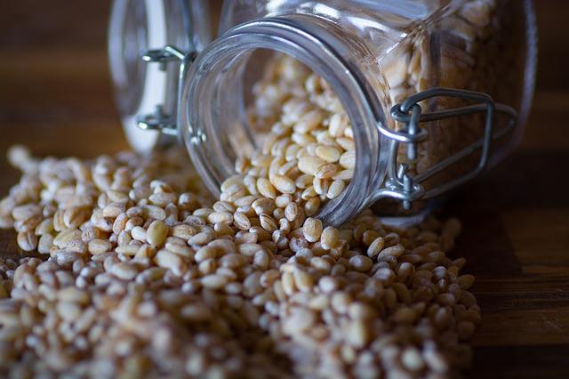 pšeničná zrna vysypaná ze sklenice.jpg